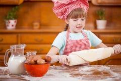 Ευτυχής χαμογελώντας αρχιμάγειρας νέων κοριτσιών στην κουζίνα που κατασκευάζει τη ζύμη Στοκ εικόνα με δικαίωμα ελεύθερης χρήσης
