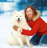 Ευτυχής χαμογελώντας γυναίκα πορτρέτου Χριστουγέννων με το άσπρο σκυλί Samoyed στο χιόνι στη χειμερινή ημέρα στοκ φωτογραφία με δικαίωμα ελεύθερης χρήσης