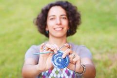 Ευτυχής χαμογελώντας γυναίκα που κάνει το τσιγγελάκι potholder υπαίθρια Στοκ Φωτογραφία