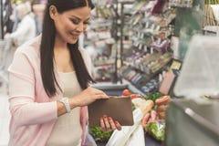 Ευτυχής χαμογελώντας γυναίκα που κρατά τη μικρή σακούλα στο κατάστημα Στοκ Εικόνα