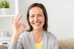 Ευτυχής χαμογελώντας γυναίκα που παρουσιάζει εντάξει σημάδι χεριών στο σπίτι Στοκ φωτογραφία με δικαίωμα ελεύθερης χρήσης