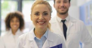 Ευτυχής χαμογελώντας γυναίκα που περπατά με την ομάδα των γιατρών στη σύγχρονη ομάδα εργαστηριακών επιτυχή ερευνητών απόθεμα βίντεο