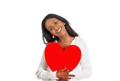 Ευτυχής χαμογελώντας γυναίκα που φαίνεται συγκινημένη κρατώντας τη μεγάλη κόκκινη καρδιά Στοκ Φωτογραφίες