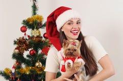 Ευτυχής χαμογελώντας γυναίκα στο καπέλο Santa με το τεριέ παιχνιδιών κοντά στα Χριστούγεννα Στοκ Φωτογραφία