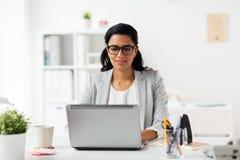 Ευτυχής χαμογελώντας επιχειρηματίας με το lap-top στο γραφείο Στοκ Φωτογραφία