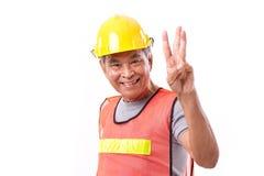 Ευτυχής, χαμογελώντας εργάτης οικοδομών που δείχνει επάνω τη χειρονομία 3 δάχτυλων Στοκ Εικόνα