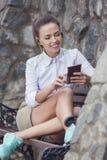Ευτυχής χαμογελώντας καυκάσια γυναίκα Brunette με τα ακουστικά που χαλαρώνουν στον πάγκο και που κουβεντιάζουν σε Smartphone Στοκ εικόνες με δικαίωμα ελεύθερης χρήσης
