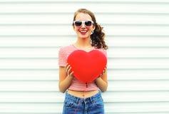 Ευτυχής χαμογελώντας νέα γυναίκα με τη μορφή καρδιών μπαλονιών αέρα που έχει τη διασκέδαση πέρα από το λευκό Στοκ Εικόνα