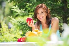 Ευτυχής χαμογελώντας νέα γυναίκα που τρώει την οργανική Apple Στοκ Φωτογραφία