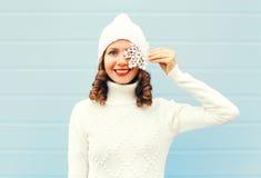 Ευτυχής χαμογελώντας νέα γυναίκα που φορά το πλεκτό πουλόβερ καπέλων με snowflakes στο πρόσωπο πέρα από το μπλε Στοκ Φωτογραφία