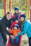 Ευτυχής χαμογελώντας νέα οικογένεια πέντε στην παιδική χαρά παιδιών ` s στο πάρκο Στοκ Εικόνες