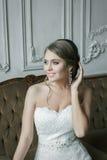 Ευτυχής χαμογελώντας νύφη ξανθή στο γαμήλιο φόρεμα η παλαιά πολυθρόνα χάρασε την εσωτερική πολυτέλεια Στοκ Εικόνα