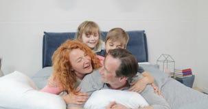 Ευτυχής χαμογελώντας οικογένεια στην ανακοίνωση παιδιών και γονέων κρεβατοκάμαρων που βρίσκεται μαζί σχετικά με τον πατέρα στο κρ απόθεμα βίντεο