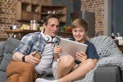 Ευτυχής χαμογελώντας συνεδρίαση πατέρων και γιων στον υπολογιστή ταμπλετών χρήσης καναπέδων, ξοδεύοντας χρονικό παιδί γονέα Στοκ Εικόνες