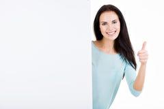 Ευτυχής χαμογελώντας όμορφη νέα γυναίκα που παρουσιάζει κενή πινακίδα Στοκ εικόνα με δικαίωμα ελεύθερης χρήσης