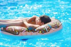 Ευτυχής χαριτωμένος έφηβος μικρών παιδιών που βρίσκεται σε ένα διογκώσιμο doughnut δαχτυλίδι στην πισίνα Ενεργά παιχνίδια στο νερ στοκ εικόνα με δικαίωμα ελεύθερης χρήσης