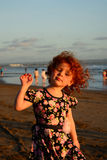 Ευτυχής χαριτωμένος λίγο redhead κορίτσι στην παραλία του Μπαλί Ηλιοβασίλεμα Στοκ Εικόνες