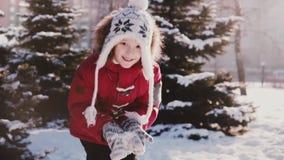 Ευτυχής χαριτωμένος εύθυμος λίγο καυκάσιο κορίτσι το χειμώνα ντύνει την εξέταση τη κάμερα ρίχνοντας έπειτα το χιόνι στον αέρα σε  φιλμ μικρού μήκους
