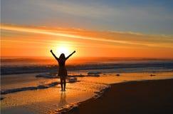 Ευτυχής χαλάρωση κοριτσιών στην ανατολή στην παραλία Στοκ εικόνες με δικαίωμα ελεύθερης χρήσης