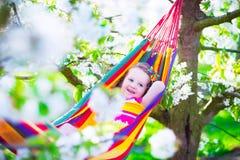 Ευτυχής χαλάρωση μικρών κοριτσιών σε μια αιώρα Στοκ φωτογραφία με δικαίωμα ελεύθερης χρήσης