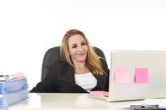 Ευτυχής χαλαρωμένη επιχειρηματίας της δεκαετίας του '40 που χαμογελά τη βέβαια εργασία στο φορητό προσωπικό υπολογιστή Στοκ εικόνες με δικαίωμα ελεύθερης χρήσης