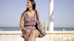Ευτυχής χαλαρωμένη καθιερώνουσα τη μόδα νέα γυναίκα στην παραλία απόθεμα βίντεο