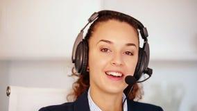 Ευτυχής χειριστής τηλεφωνικών κέντρων που μιλά με τον πελάτη και το χαμόγελο απόθεμα βίντεο