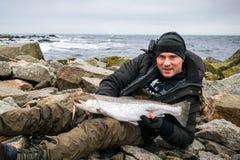 Ευτυχής ψαράς με τη μεγάλη πέστροφα θάλασσας Στοκ Εικόνες