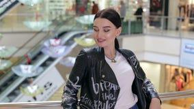Ευτυχής όμορφη γυναίκα με τις στάσεις τσαντών αγορών στο κατάστημα απόθεμα βίντεο