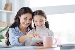 Ευτυχής όμορφη γυναίκα που διαβάζει ένα βιβλίο με την κόρη της Στοκ Εικόνες