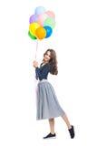 Ευτυχής όμορφη γυναίκα που κρατά τα ζωηρόχρωμα μπαλόνια απομονωμένα στο μόριο στοκ εικόνες με δικαίωμα ελεύθερης χρήσης