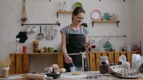 Ευτυχής όμορφη γυναίκα που προετοιμάζει τα τρόφιμα στην κουζίνα και που μιλά στο κινητό τηλέφωνο φιλμ μικρού μήκους