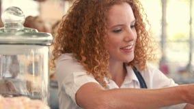 Ευτυχής όμορφη γυναίκα που προετοιμάζει το πιάτο του κέικ φιλμ μικρού μήκους