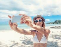 Ευτυχής όμορφη γυναίκα που χρησιμοποιεί το κινητό τηλέφωνο στην τροπική παραλία, tak Στοκ Εικόνες
