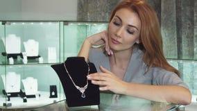 Ευτυχής όμορφη γυναίκα σχετικά με το περιδέραιο διαμαντιών που χαμογελά χαρωπά φιλμ μικρού μήκους