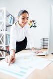 Ευτυχής όμορφη επιχειρηματίας που δείχνει το δάχτυλο στη γραφική έκθεση Στοκ φωτογραφία με δικαίωμα ελεύθερης χρήσης
