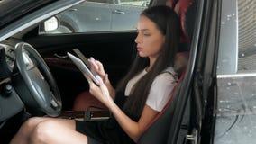 Ευτυχής όμορφη επιχειρηματίας που χρησιμοποιεί τον υπολογιστή ταμπλετών μέσα σε ένα αυτοκίνητο απόθεμα βίντεο
