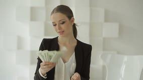 Ευτυχής όμορφη επιχειρηματίας στο επίσημο κοστούμι που εξιστορεί το σωρό των δολαρίων απόθεμα βίντεο
