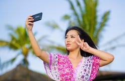 Ευτυχής όμορφη και πανέμορφη ασιατική κινεζική γυναίκα στο φόρεμα γοητείας που παίρνει τη φωτογραφία αυτοπροσωπογραφίας selfie με Στοκ Εικόνες