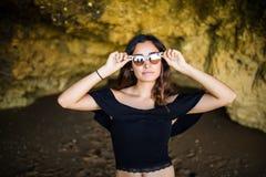 Ευτυχής όμορφη λατινική γυναίκα που φορά το χαμόγελο γυαλιών ηλίου πλησίον στο ro Στοκ Εικόνες