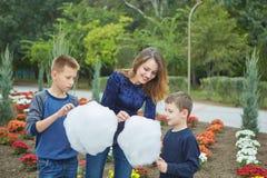 Ευτυχής όμορφη μητέρα και δύο γιοι τρώνε την καραμέλα βαμβακιού στοκ εικόνα