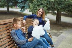 Ευτυχής όμορφη μητέρα και δύο γιοι τρώνε την καραμέλα βαμβακιού στοκ εικόνες