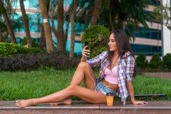 Ευτυχής όμορφη νέα γυναίκα με τα γυμνά πόδια που κάθονται στη συγκράτηση πετρών στο πάρκο και που ακούνε τη μουσική στα ακουστικά Στοκ Φωτογραφία