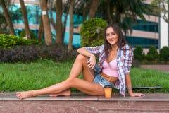 Ευτυχής όμορφη νέα γυναίκα με τα γυμνά πόδια που κάθονται στη συγκράτηση πετρών στο πάρκο και που ακούνε τη μουσική στα ακουστικά Στοκ Εικόνες