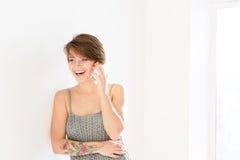 Ευτυχής όμορφη νέα γυναίκα που γελά και που μιλά στο κινητό τηλέφωνο Στοκ Φωτογραφία
