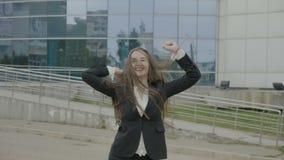 Ευτυχής όμορφη νέα επιχειρηματίας που φορά την εξάρτηση γραφείων που χορεύει χαρωπά στη φύση μπροστά από την εταιρία - απόθεμα βίντεο
