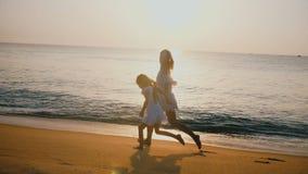 Ευτυχής όμορφη νέα μητέρα και λίγη κόρη που τρέχουν μαζί να κρατήσει τα χέρια, που χαλαρώνουν στην επική παραλία θάλασσας ηλιοβασ φιλμ μικρού μήκους