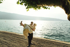 Ευτυχής όμορφη νύφη εκμετάλλευσης νεόνυμφων στα όπλα του στην παραλία στο sunse Στοκ εικόνες με δικαίωμα ελεύθερης χρήσης