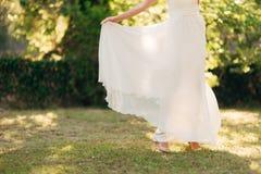 Ευτυχής όμορφη νύφη υπαίθρια Κυματισμός γαμήλιων φορεμάτων Στοκ Φωτογραφία
