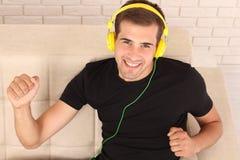 Ευτυχής όμορφη συνεδρίαση ατόμων στον καναπέ με τα ακουστικά και liste στοκ εικόνες με δικαίωμα ελεύθερης χρήσης